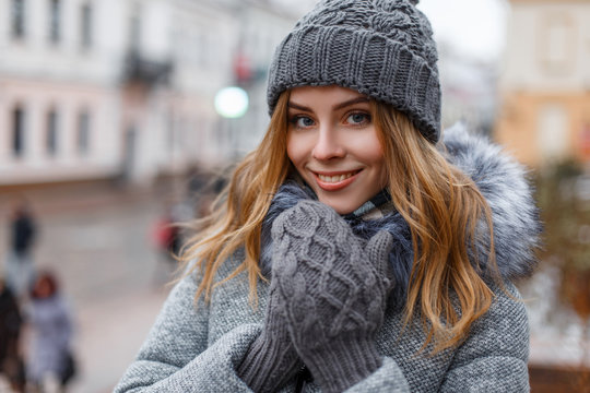 Portrait of a wonderful young woman with beautiful blue eyes with natural make-up in a sweet smile in a knitted hat in knitted mittens in a stylish coat on the background of city streets. Happy girl.
