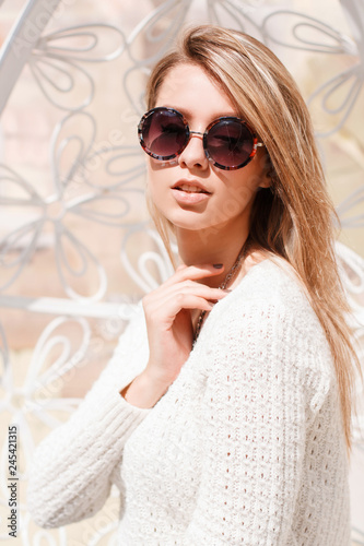 b5c839999 Portrait of an attractive hipster young woman in a fashionable vintage  sweater in round stylish sunglasses on a white background.