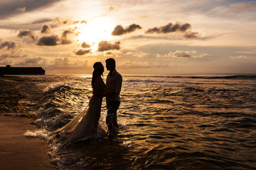 Silhouettes of the bride and groom look at each other standing in the sea water on the beach at sunset