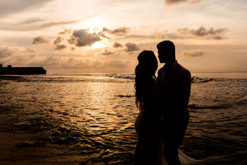 Silhouettes of bride and groom embracing look at each other on the beach at sunset
