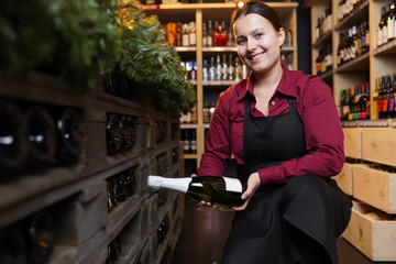 Image of woman with bottle of wine squatting
