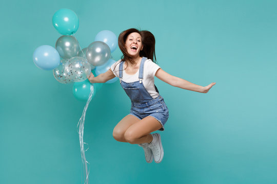 Portrait of pretty funny young woman in denim clothes jumping high celebrating and holding colorful air balloons isolated on blue turquoise background. Birthday holiday party, people emotions concept.