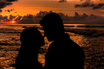 Silhouettes girls and men touch each other noses on the beach at sunset