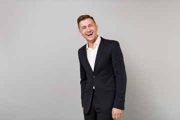 Portrait of handsome laughing young business man in classic black suit, white shirt standing isolated on grey wall background in studio. Achievement career wealth business concept. Mock up copy space.