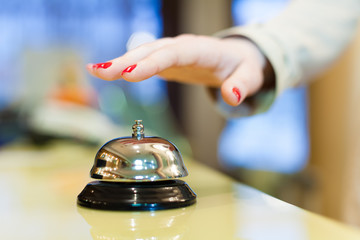 A female hand ringing silver service bell