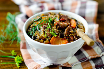 Beef stew with vegetables in a bowl on a wooden table
