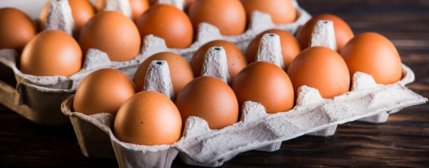 Fresh brown eggs on rustic table.