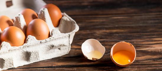 Fresh brown eggs on rustic table. Broken egg with yolk.