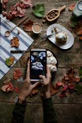 Young woman make photo of Cinnamon rolls on wooden table with mobile phone.