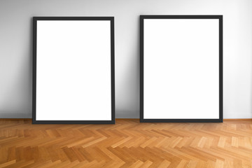 two empty picture frames on wooden parquet floor white wall background  , blank frame