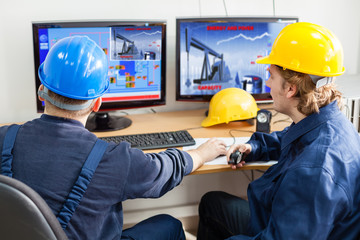 Engineers in the control room, looking at computer monitor.Image of a pump jack at monitor is mine property,mine own work