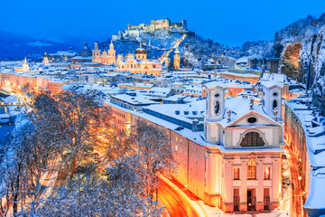 Salzburg, Austria: Winter view of the historic city of Salzburg with famous Festung Hohensalzburg and Salzach river illuminated in beautiful twilight during scenic Christmas time in winte