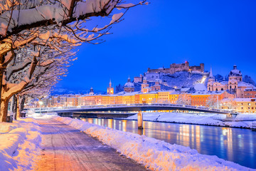 Salzburg, Austria: Winter viewof the historic city of Salzburg with famous Festung Hohensalzburg and Salzach river illuminated in beautiful twilight during scenic Christmas time in winter