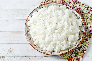 Boiled rice in a plate on a white wooden table