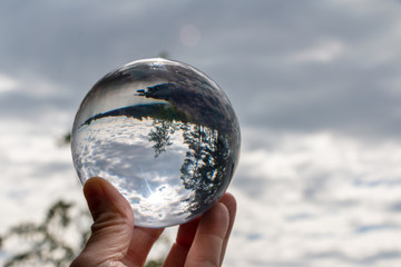 hand holding acrylic crystal ball by a lake