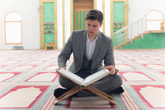 Religious muslim man praying inside the mosque and reading holy book koran.