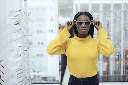 Young afro american woman wear sunglasses for buy in optical shop.
