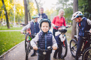 Theme family sports vacation in park in nature. big friendly Caucasian family of six people mountain bike riding in forest. Children brothers and sister stand on the background of parents in a row