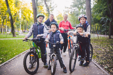 Theme family sports vacation in park in nature. big friendly Caucasian family of six people mountain bike riding in forest. Children brothers and sister stand on the background of parents in a row Papier Peint