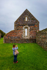 Woman Taking a Photo of the Iona Nunnery