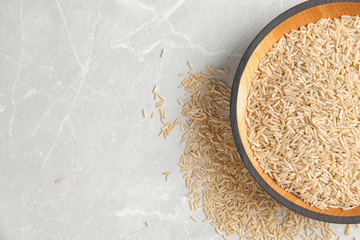 Bowl with raw unpolished rice on light background, top view. Space for text