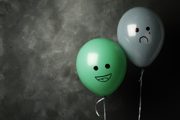 Balloons with drawings of sad and happy faces on dark background, space for text. Depression symptoms