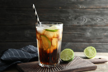 Glass of cocktail with cola, ice and cut lime on table