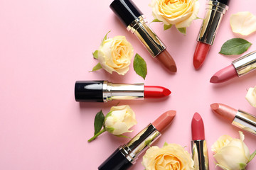 Flat lay composition with lipsticks and roses on color background. Space for text