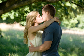 Loving young couple kissing under tree on walk in countryside