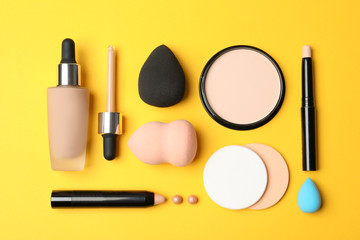 Flat lay composition with skin foundation, powder and beauty accessories on color background