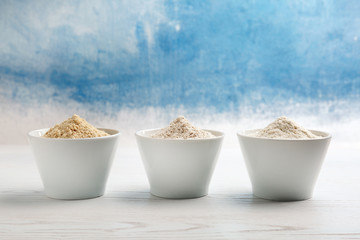 Bowls with different types of flour on table against color background. Space for text