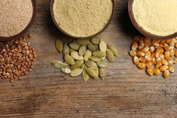 Flat lay composition with different types of flour and seeds on wooden background