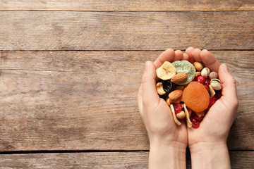 Woman holding different dried fruits and nuts on wooden background, top view. Space for text
