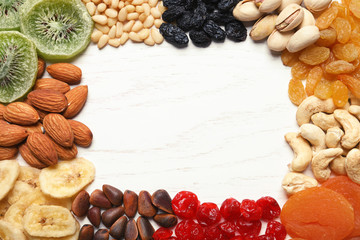 Frame of different dried fruits and nuts on wooden background, top view. Space for text