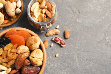 Flat lay composition of different dried fruits and nuts on color background. Space for text