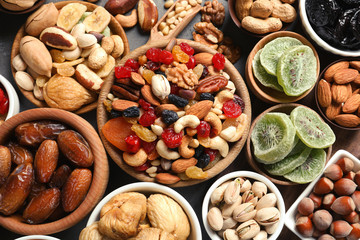 Flat lay composition of different dried fruits and nuts on table