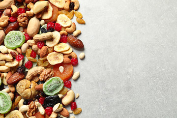 Different dried fruits and nuts on color background, top view. Space for text