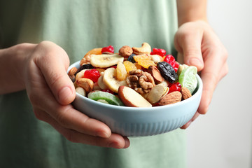 Young woman holding plate with different dried fruits and nuts, closeup