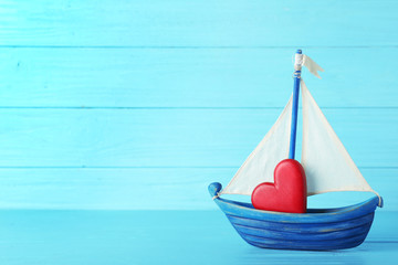 Toy boat with red heart on table against color background. Space for text Wall mural