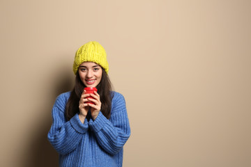 Young woman in sweater with cup of hot coffee on color background, space for text. Winter season