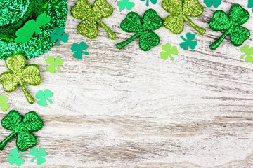 St Patricks Day corner border of shamrocks with leprechaun hat over a rustic white wood background Wall mural