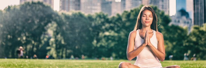 Yoga woman meditation praying outside in city park wellness banner panorama .Summer exercise lifestyle active young Asian girl meditating background.