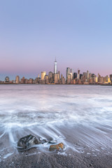 View on Financial District at sunrise from hudson river beach with long exposure