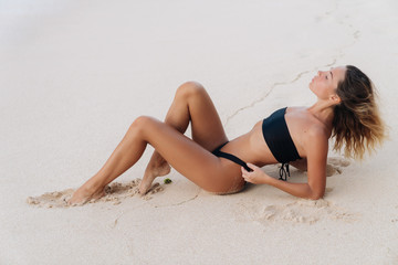 Sexy tanned model in black swimsuit posing on white sandy beach