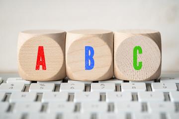 """Würfel mit Buchstaben """"ABC"""" auf Tastatur"""