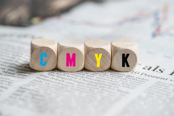 """Buchstaben """"CMYK"""" auf Würfeln in den entsprechenden Farben auf einer Zeitung liegend"""