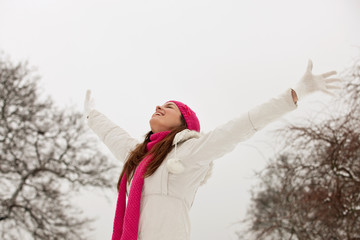 Young woman in winter landscape standing with outstretched arms