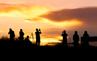 silhouette of traveler taking picture of landscape during sunrise.