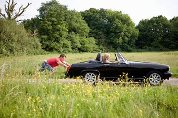 Man pushing woman in broken down classic sports car on country road
