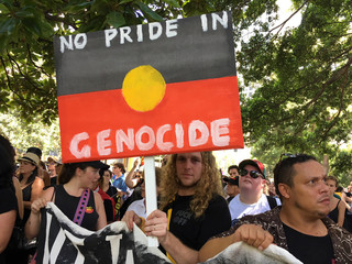 A man holds up a sign in the colours of the Australian Aboriginal flag during a demonstration on Australia Day in Sydney